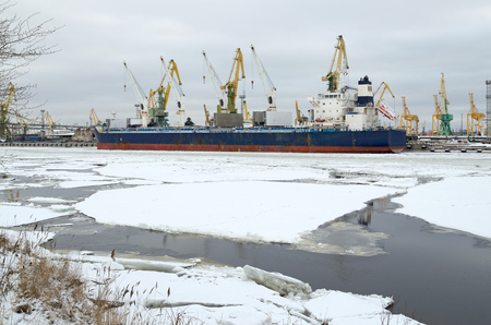 In the port of the river is covered with ice.The ships are berthed.Them loaded with goods. Stock Photo