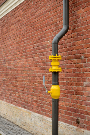 Along the wall there is a gas pipe.On the pipe the valve is installed.