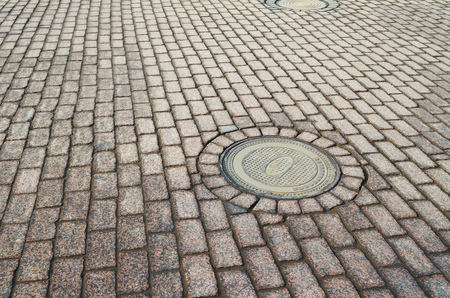 The pavement is tiled. On the surface hatch to the underground sewer. Banco de Imagens
