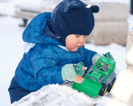 The child was taken for a walk.The boy enjoys the winter weather.