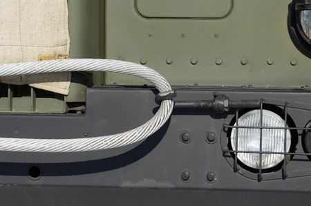 The bumper of a military vehicle.On it hangs a metal cross.