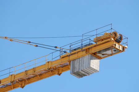 Tower cranes on the construction of houses .They lift heavy loads at the top. Stock Photo