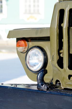 A headlight on a military truck.In the dark, the headlight illuminates the road.