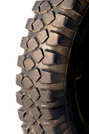 Rubber car tyre on white background.With a pronounced texture. Stock Photo