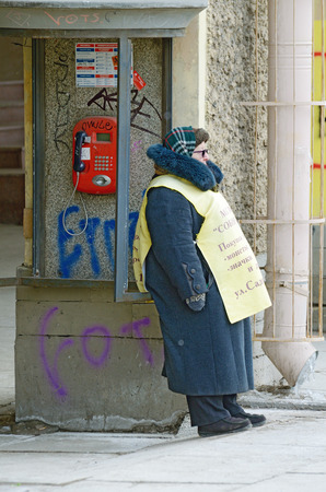 Saint-Petersburg.Russia.March.3.2018.The work of advertising agents.Grandma is standing on the street with a Billboard.She invites passers-by to the store. Editorial