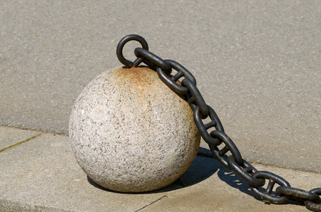 Stone balls lie on the sidewalk.They serve as a decorative fence. Stock Photo