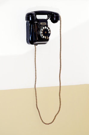 Vintage phone hanging on the wall.The device serves as a means of communication between people.