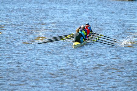 Ein Team von Ruderern in einem Sportboot. Das Training findet auf dem Fluss statt.
