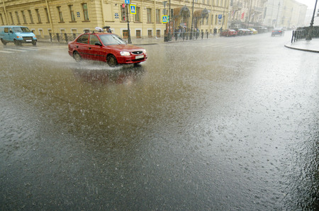 It is raining heavily in the city.On the roads are large puddles.