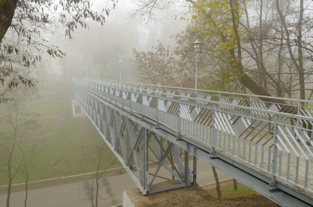 Iron bridge over the river.Around is a dense fog. Stock Photo