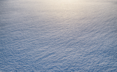 Oblique rays of the sun reflect the texture of snow. Stock Photo