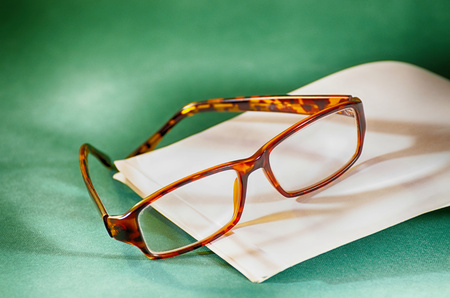 Glasses and a book lying on a table covered with green cloth. Stock Photo