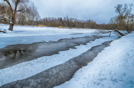 Snowy winter in the forest.The lake was covered with ice.Its snowing.