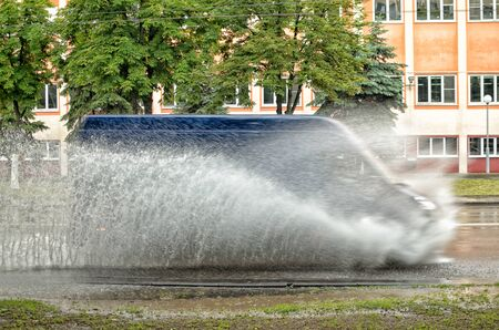 Cars move on asphalt through a huge puddle.Splashes from puddles razletayutsya in different directions.