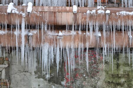 Icicles hang on the heating main.From the warmth start to drip icicles.
