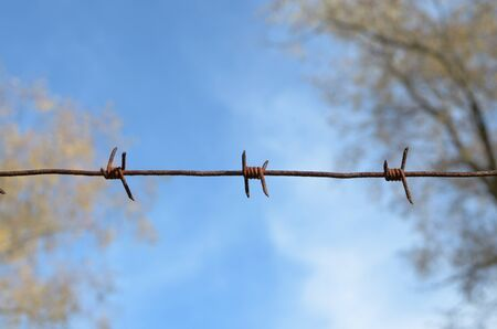 Barbed wire against the sky.This is an artificial barrier.