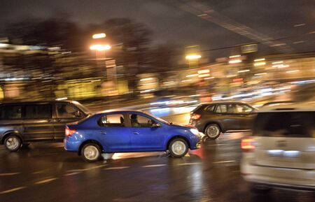 High-speed car driving.On the streets of the city glow electric lights. Imagens