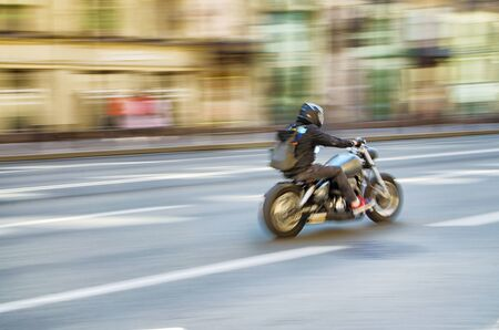 Fast motorcycle riding on a city street.