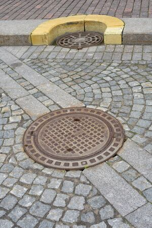 Sewer manhole on a city road.This is a heavy iron cover. Archivio Fotografico