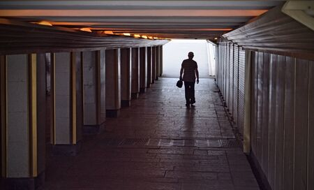 A man goes through an underpass.This is a safe way to cross the roadway.