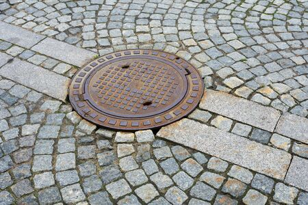 Sewer manhole on a city road.This is a heavy iron cover. Foto de archivo - 150125666