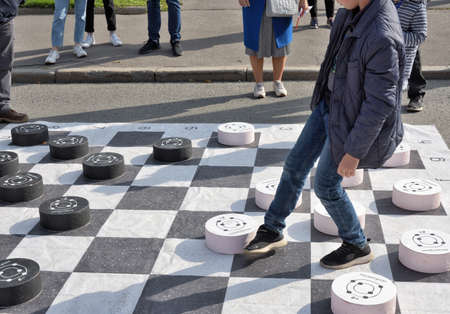 Russia, Saint Petersburg, September 20, 2020.Children play checkers on a large playing field. The game helps to develop logic and thinking in children.