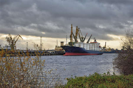 Large containers are loaded onto the ship by cranes. Reklamní fotografie
