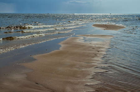 Sandy beach by the sea.Warm waves wash over the shore. Reklamní fotografie