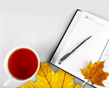 Notepad with pen, white cup with a beverage, and yellow wedge leaves.