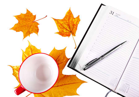 Notebook silver pen, empty mug of red color for a drink, isolated on a white background with yellow leaves. 版權商用圖片