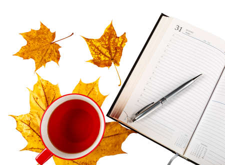 Cup tea notepad pen, yellow leaves are isolated on a white background. 版權商用圖片