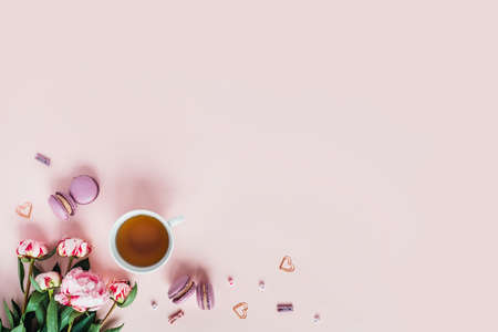 Pink background with macaroons and a Cup of tea surrounded by peonies. Top view with space for your text.