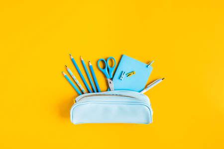 Schulsachen: Bleistifte Schere Notizblock Stiftetui auf gelbem Hintergrund. Standard-Bild