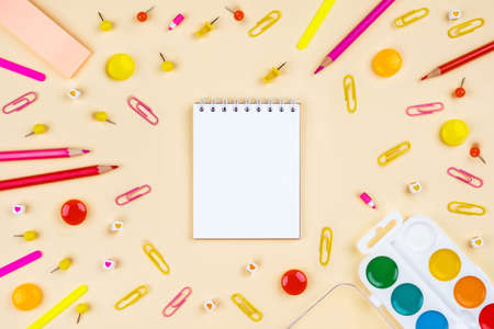 Back to school creative template with pencils, clips and watercolor. Composition in yellow and red colors. Flat lay, top view.