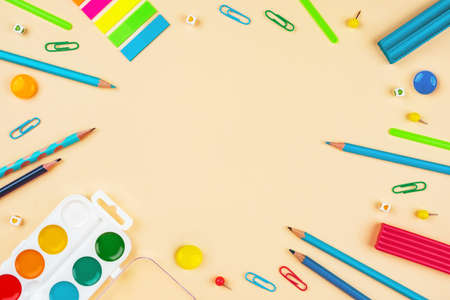 Back to school creative template with pencils, clips and watercolor. Composition in blue and red colors.