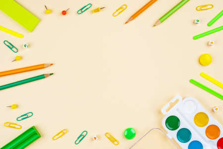 Back to school creative template with pencils, clips and watercolor. Composition in green and yellow colors.
