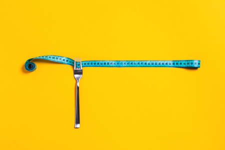 Sports and diet picture. Green measuring tape wound around the fork. Stock Photo