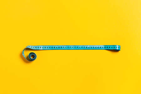 Sports and diet picture. Green measuring tape on color background. Flat lay, top view.