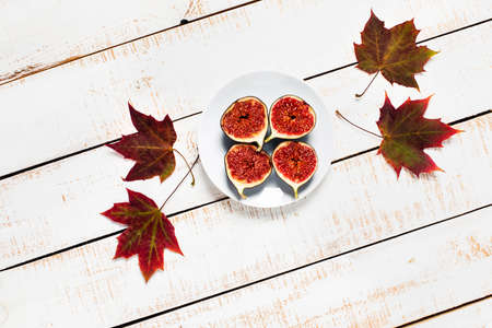 Autumn, fall concept. Figs, maple leaves a white wooden background. Space for your text. Flat lay, top view. Stock Photo