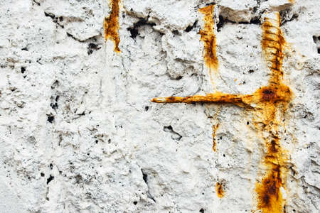 A white stone wall with rusty bits of rebar sticking out. Stock Photo