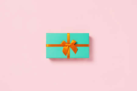 Orange bow on a mint box located on pink background. Stock Photo