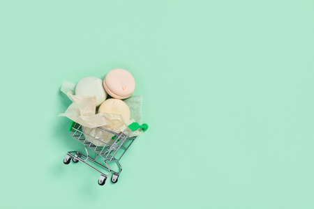Food mint concept. Tasty marshmallows wrapped in paper transported on a shopping cart. Flat lay, top view. Фото со стока