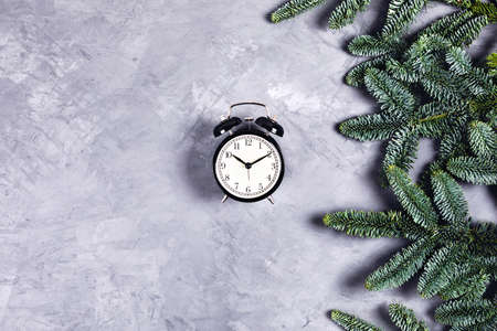 Christmas and new year composition. Black vintage clock with alarm on gray concrete background with Christmas branches. Flat lay, top view, copy space.