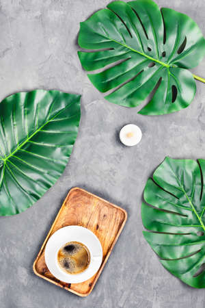 Grey concrete background with wooden tray and cup of espresso surrounded by tropical leaves. Flat lay, top view. Spa concept. Banque d'images - 133065788