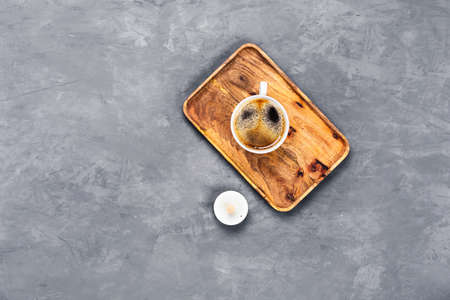 Cup of coffee on wooden tray with plate on gray concrete background. Flat lay, top view, copy space. Banque d'images - 133066057