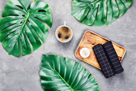 Grey concrete background with wooden tray and black towels and cup of espresso surrounded by tropical leaves. Flat lay, top view. Spa concept.