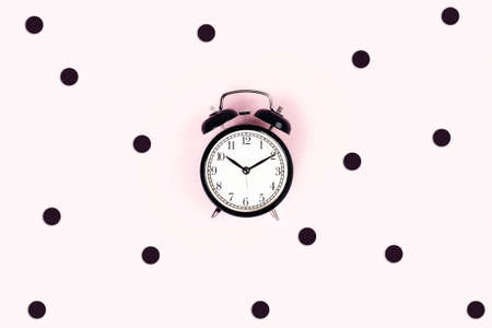 Alarm vintage clock on a pink background surrounded by confetti. Flat lay, top view, copy space.