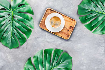 Gray concrete background with wooden tray and cup of espresso surrounded by tropical leaves. Flat lay, top view. Spa concept.
