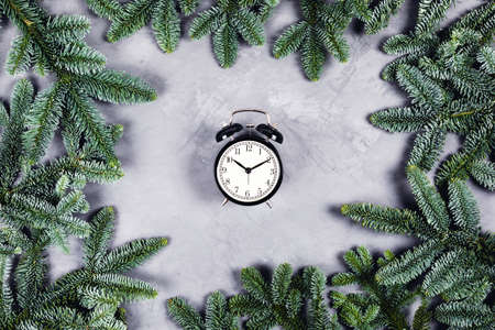 Christmas and new year composition. Black vintage clock with alarm on gray concrete background surrounded by Christmas branches. Flat lay, top view.