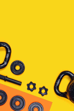 Sports concept background. Kettlebells and dumbbells on yellow and orange background. Flat lay, top view, copy space. Stock Photo - 135502410